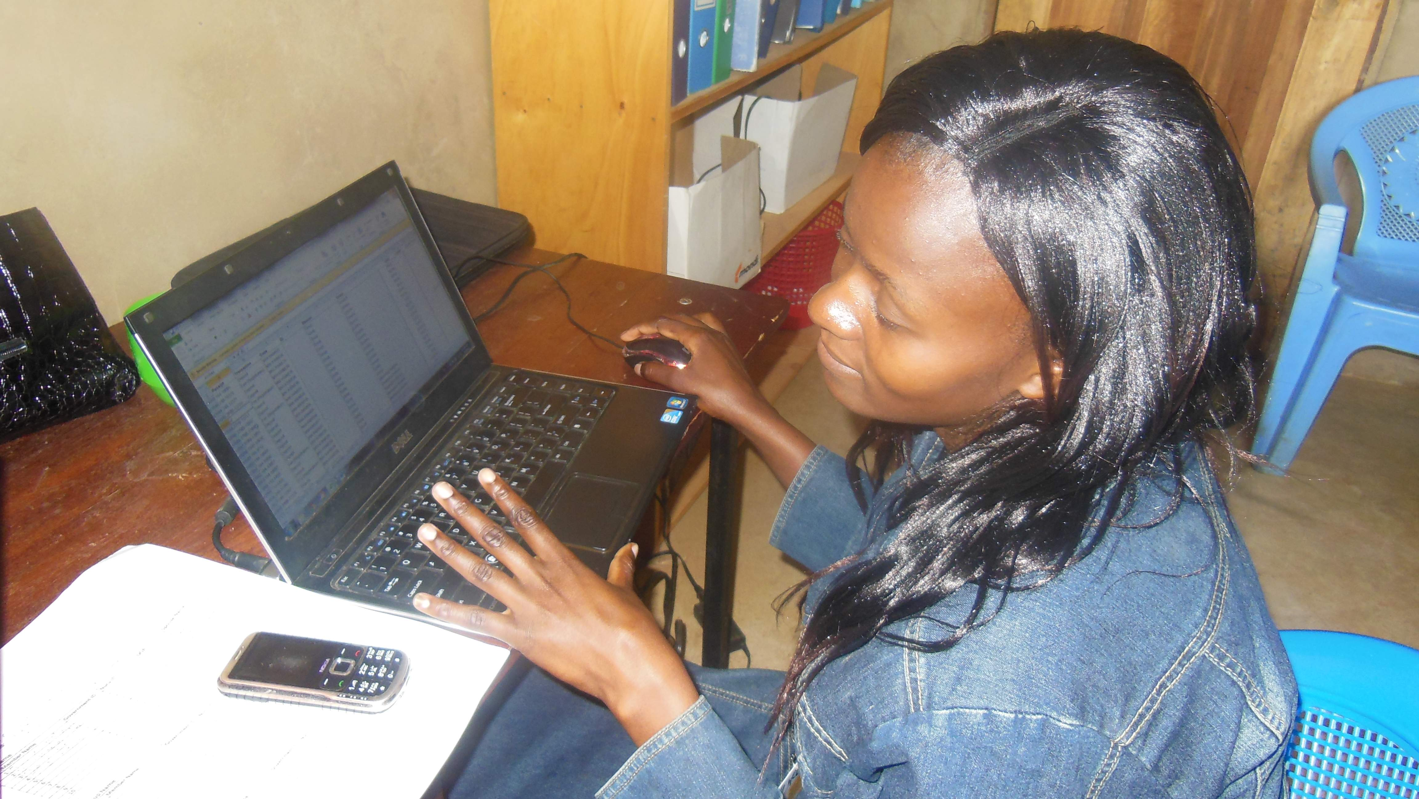 Christine Alvitsa, Nuru Kenya Financial Inclusion Program Information Systems Specialist, enters data into Mifos at the Nuru Kenya office.