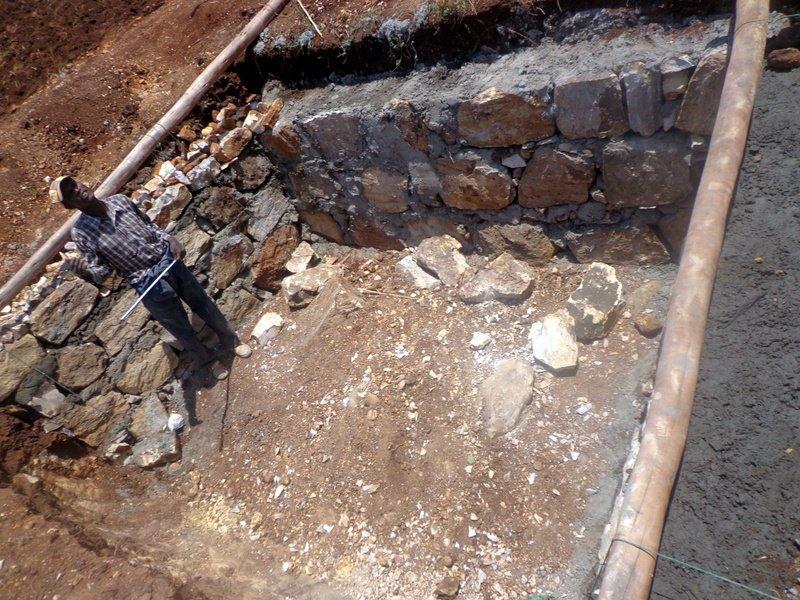 Local contractor checking measurements of latrine foundation