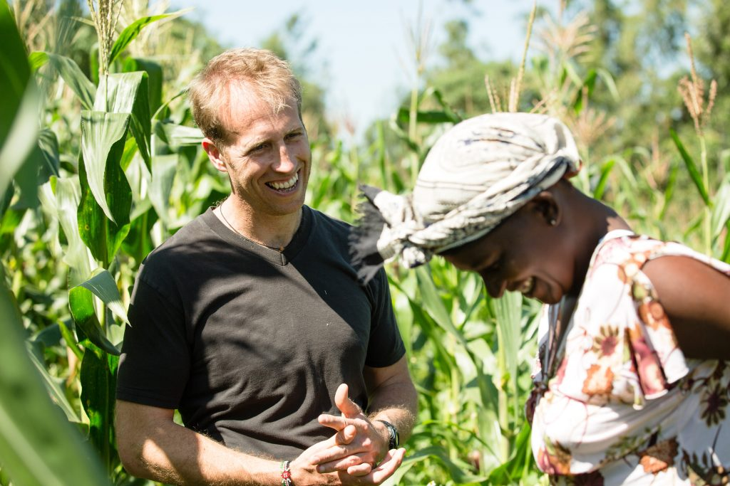 man laughing in a field of corn with a woman farmer in Kenya